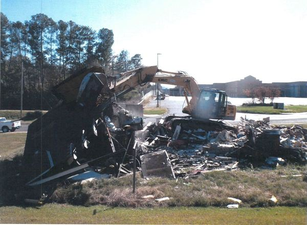 bulldozer cleaning up destroyed house